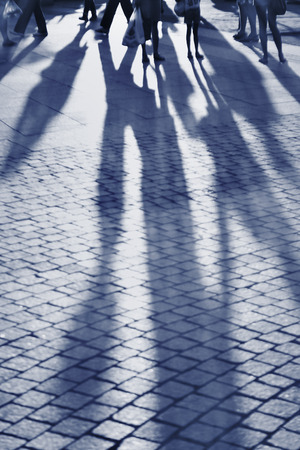 silhouettes of people on the cobblestone pavement, blue color tone
