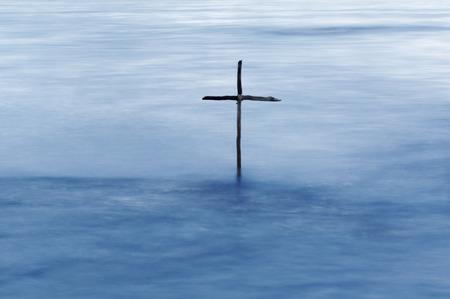 battesimo: simbolo del battesimo, una croce di legno nel fiume Giordano