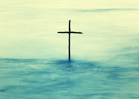 cross: symbol of Baptism, a wooden cross in the Jordan River