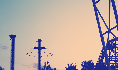 amusement park with swing ride at sunset, retro vintage style effect Stock Photo