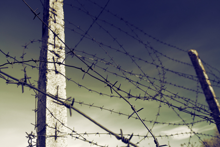 concept of a military theme - barbed wire against the gloomy sky, vintage color effect Stock Photo