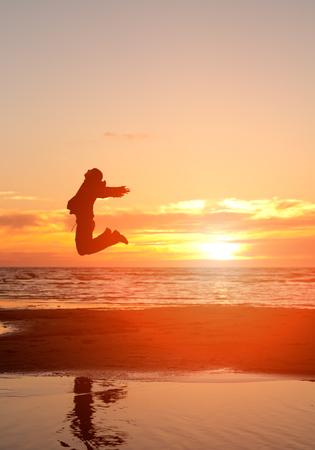 happy man jump on a beach at sunrise Imagens