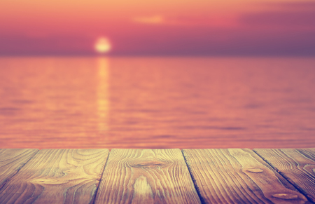wooden desk and blurred summer background, sunset on the lake
