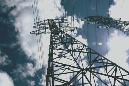 power line towers against blue sky, vintage color effect