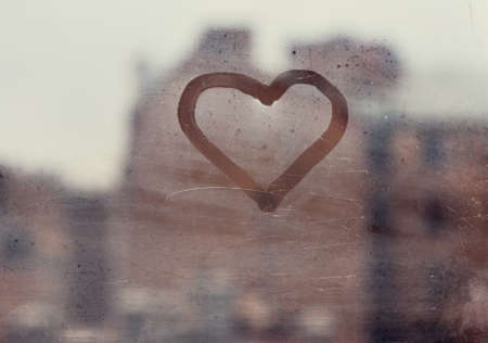 love concept, heart silhouette on a window glass in an old european town