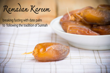 date palm on the cloth with message for vintage background. Fasting is obligatory for adult Muslim in Ramadan. Muslim will breaking their fasting after sundown with a date palm or with water to  following the tradition of Sunnah.