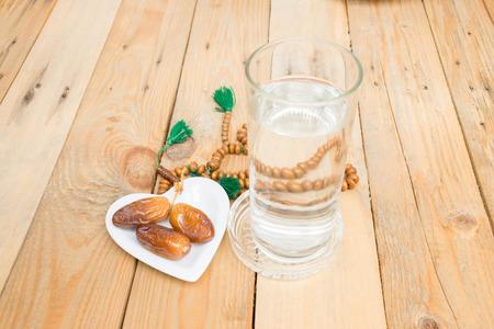 枣椰子在木头上。斋戒是斋月中成人穆斯林的强制性。穆斯林将在日落往风或用水以追随传统之后打破他们的禁食。