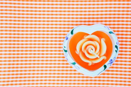 scotch: candles heart shape on orange scotch fabric background