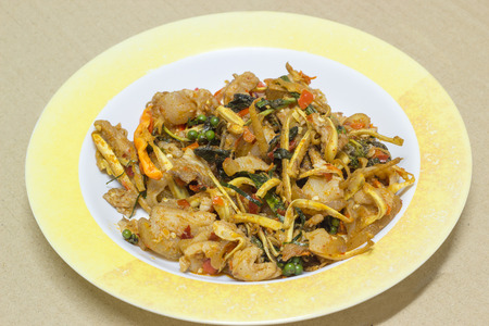 Stir Fried Wild Boar with Red Curry in plastic dish on card board background photo