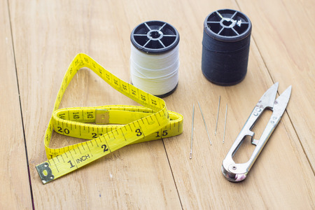 alterations: measuring tape scissor and thread on wooden board