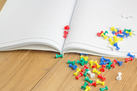 tack board: colorful tack with notebook on wooden board Stock Photo