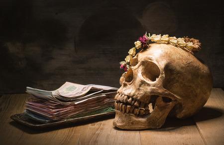 pile of money: human skull garland jasmine and pile money still life