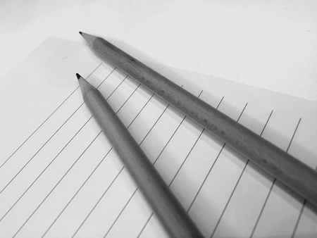 grey scale: Two wooden pencils with white paper and lines in grey scale