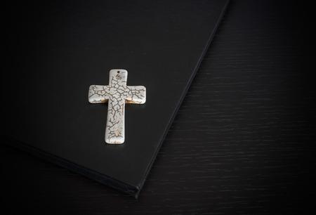 Grunge white bone Cross on the book Easter or Christian beliefs photo