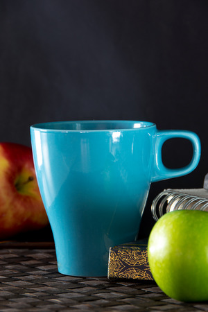 Hot drink in Light Blue  cup and apple photo