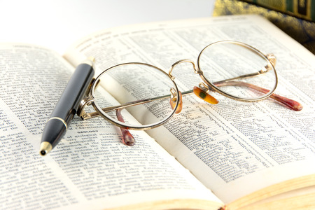 books with eye glasses and pen photo