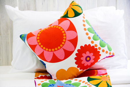 bedside: colorful pillow on a bed in a bedroom Stock Photo