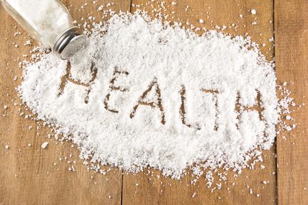 glass salt shaker  on wooden and health word on salt