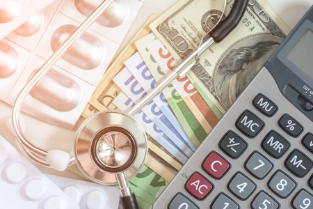 Stethoscope with Banknote and calculator for health care costs or medical insurance Stock Photo