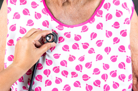 Doctor using stethoscope to checking to elderly woman patient