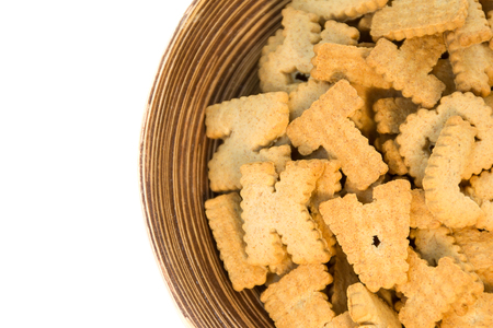 alphabet shaped biscuits in wood plate on white background