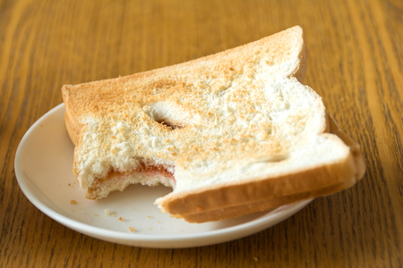 bitten bread in a white plate on wooden table Stock Photo