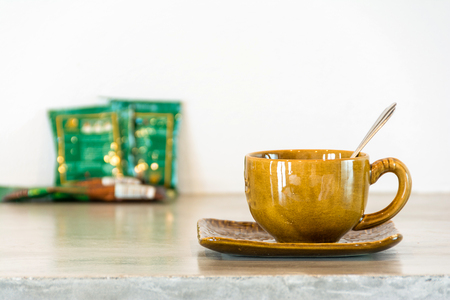 coffee cup with  instant coffee pack in background blur