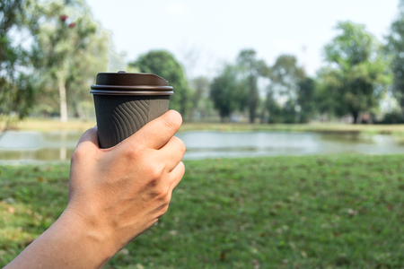 hand holding gray paper cup of hot coffee in nature background.