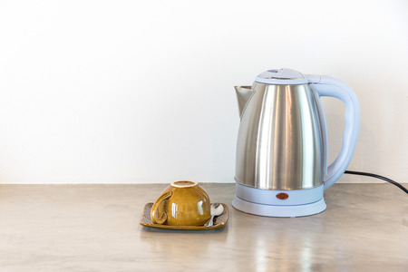 Metal electric kettle with brown cup Stock Photo