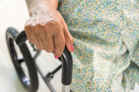 elderly woman holding walking stick and sitting in wheelchair