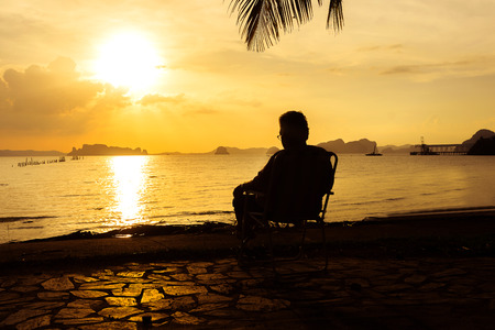elderly woman sitting alone in chair looking at sunset Stock Photo