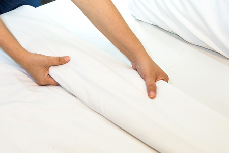 Hand set up white bed sheet in bedroom