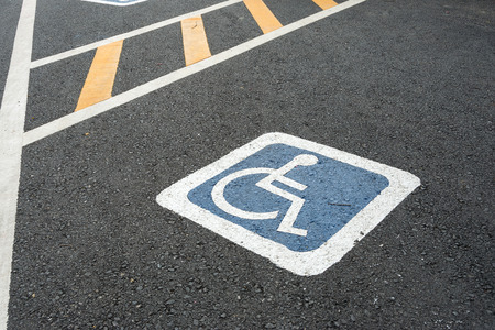 Handicap symbol on road parking areas reserved for disabled people