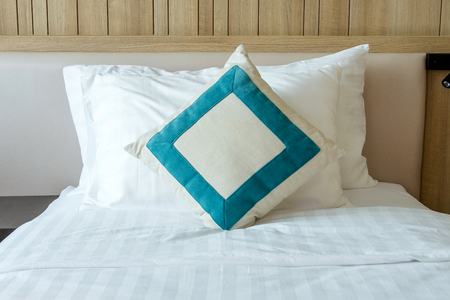 Messy white bed comforter with decorative pillows in bedroom