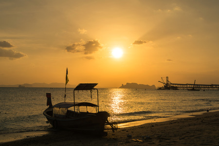 Silhouette fishing boat on the beach and island during sunrise Stock Photo
