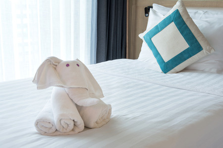 Towels in elephants shape with blue pillow on white  bed Comfortable soft Stock Photo