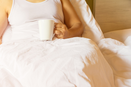 woman holding coffee cup on bed in the morning