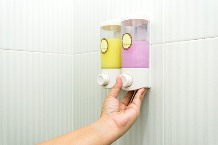 Hand pumping Liquid soap and shampoo dispenser in a bathroom Stock Photo