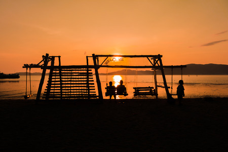 Silhouette of a family enjoying swing at sunset beach