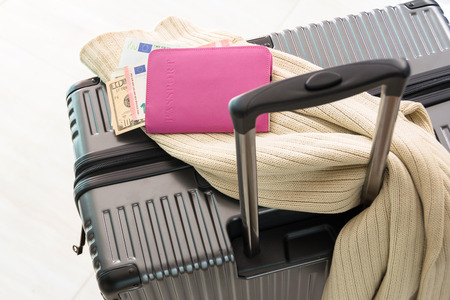 Traveling luggage in airport terminal with passport,money and Sweater.travel concept