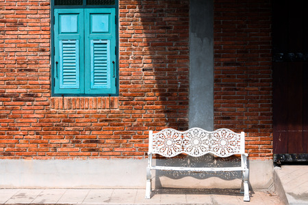 white bench with vintage brick wall and blue window