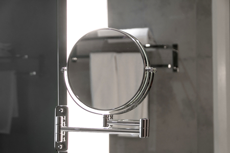 Round bathroom mirror on shaving mirror Stock Photo