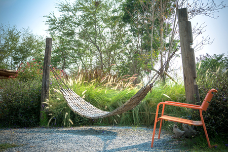 wooden swing and orange  chairs in the garden