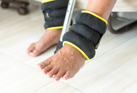 elderly exercising with ankle weights for strengthening legs Stock Photo