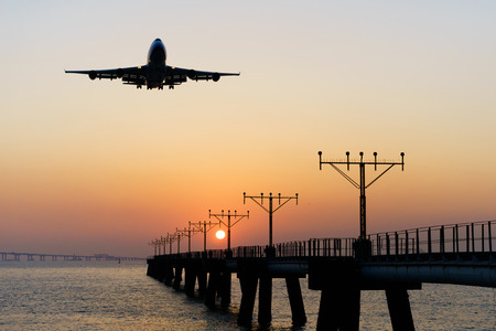 Silhouette of an airplane landing at Hong Kong airport during sunset