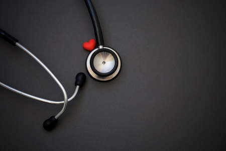 Stethoscope and red heart on black background. Cardiology concept. World health day and healthcare concept.