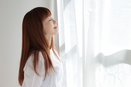woman face close up: Beautiful young Asian woman by the window Stock Photo