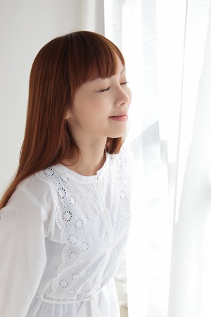 Beautiful young Asian woman by the window 写真素材