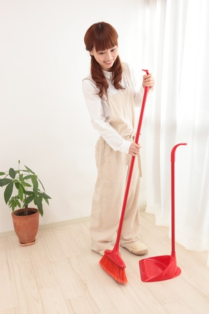 Young Asian woman with a broom to clean up photo