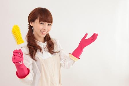 クリーニング ツールを持つ若いアジア女性